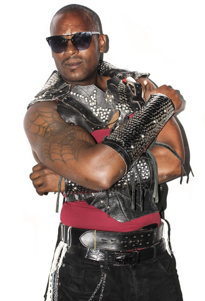 a photo of a Botswanan man with bald head, tattoos and sleeveless leather jacket