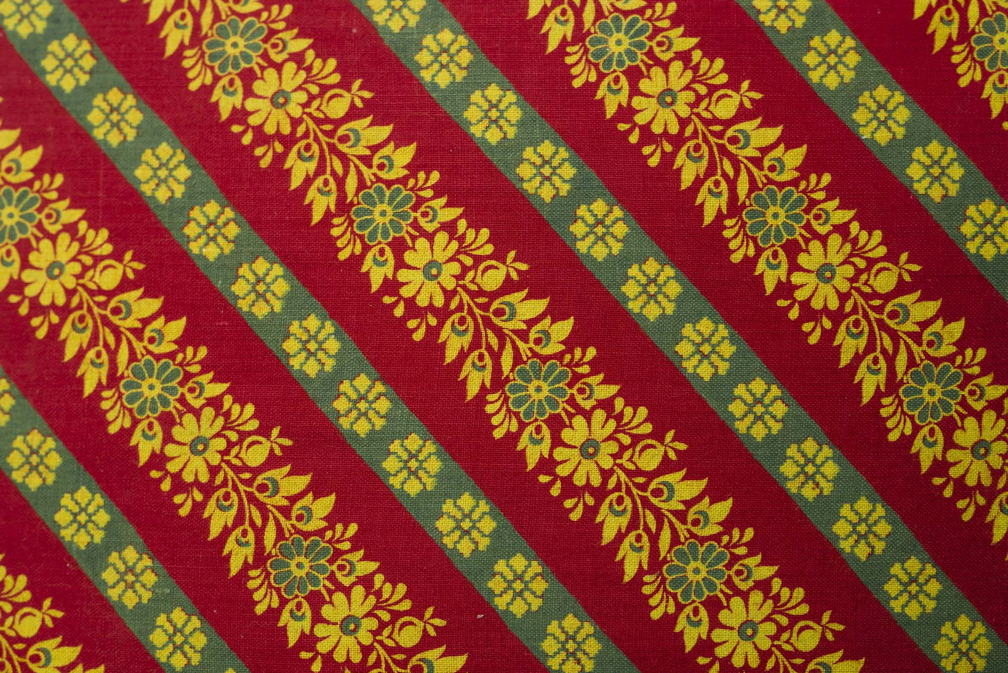 a tetxtile sample with rows of floral patterns against a red background coloured cloth