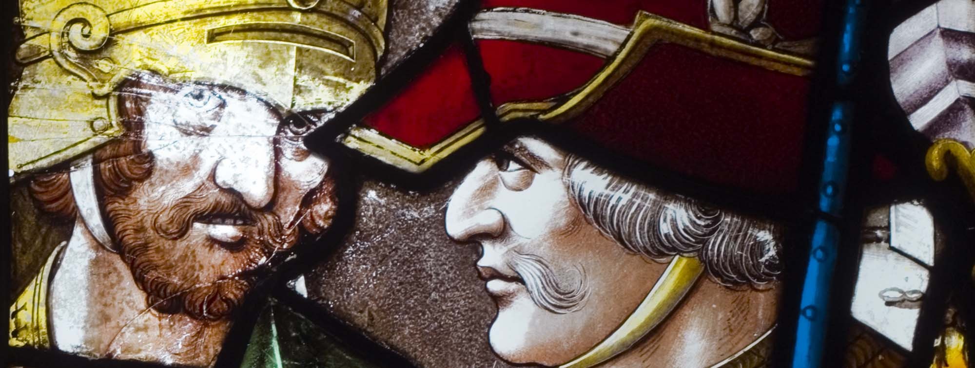 a close up of a tained glass panel showing the faces of two men