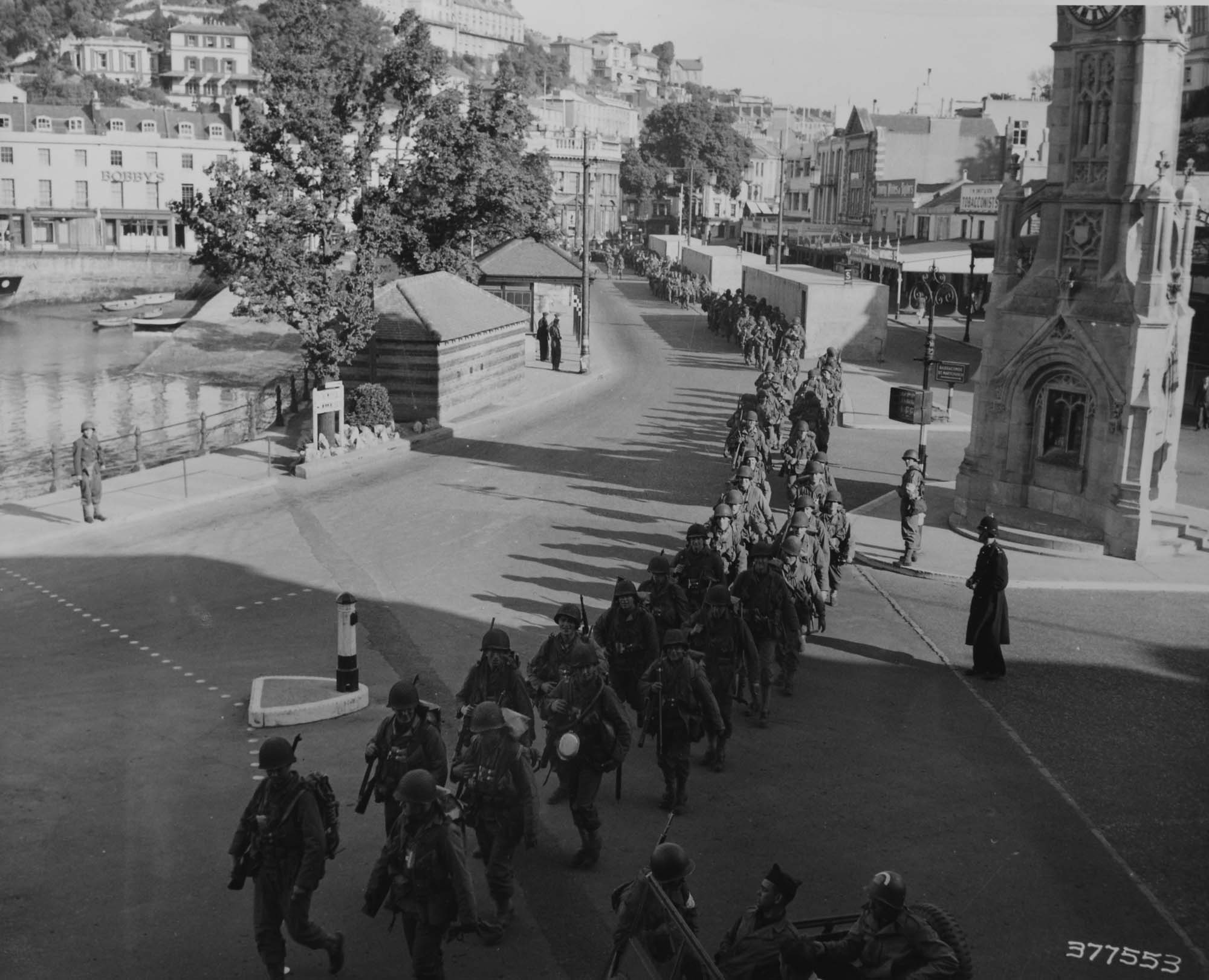a black and white photo US troops marching along a British seafront