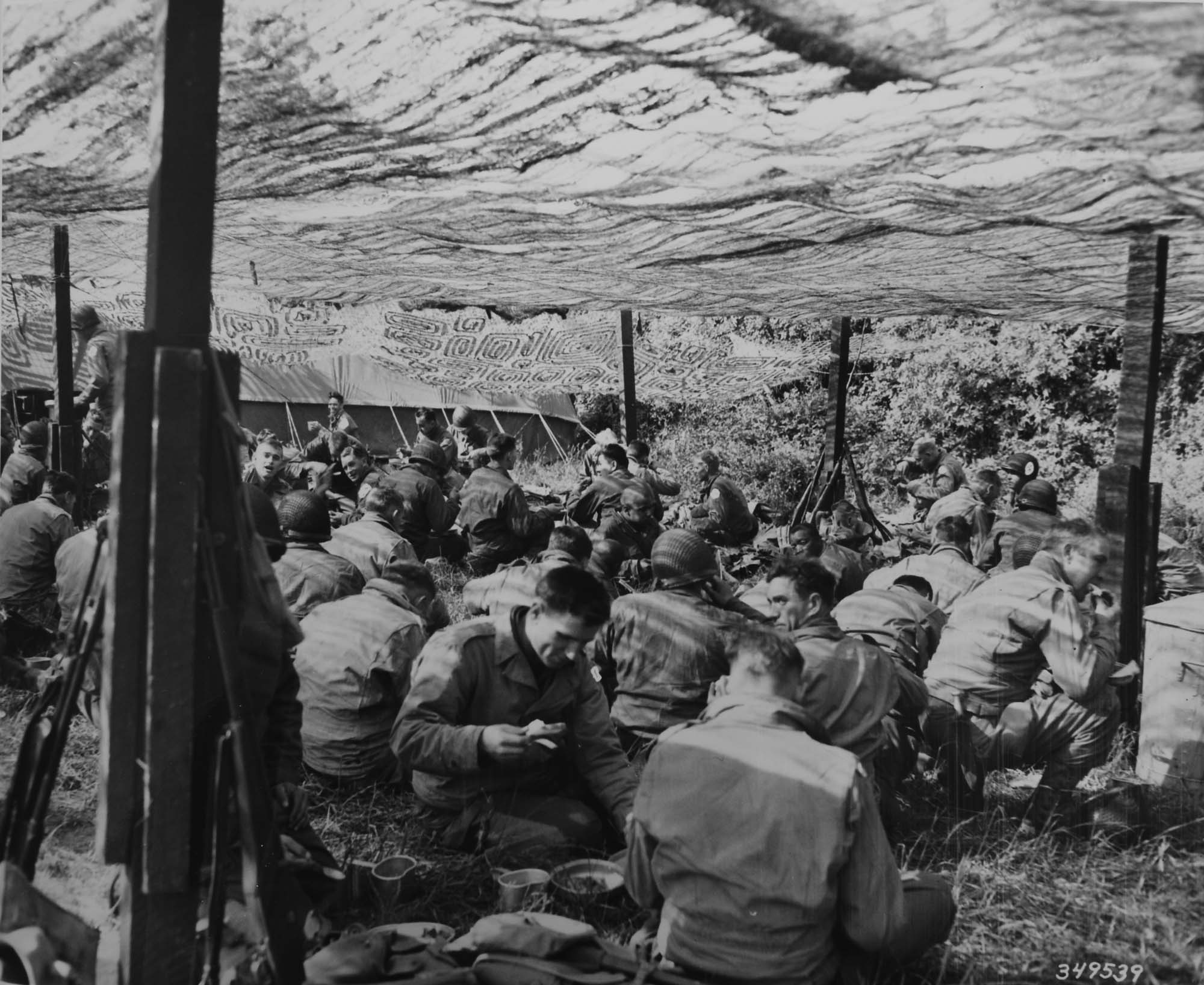 a photo of a large group of seated soldiers eating beneath a camouflage net