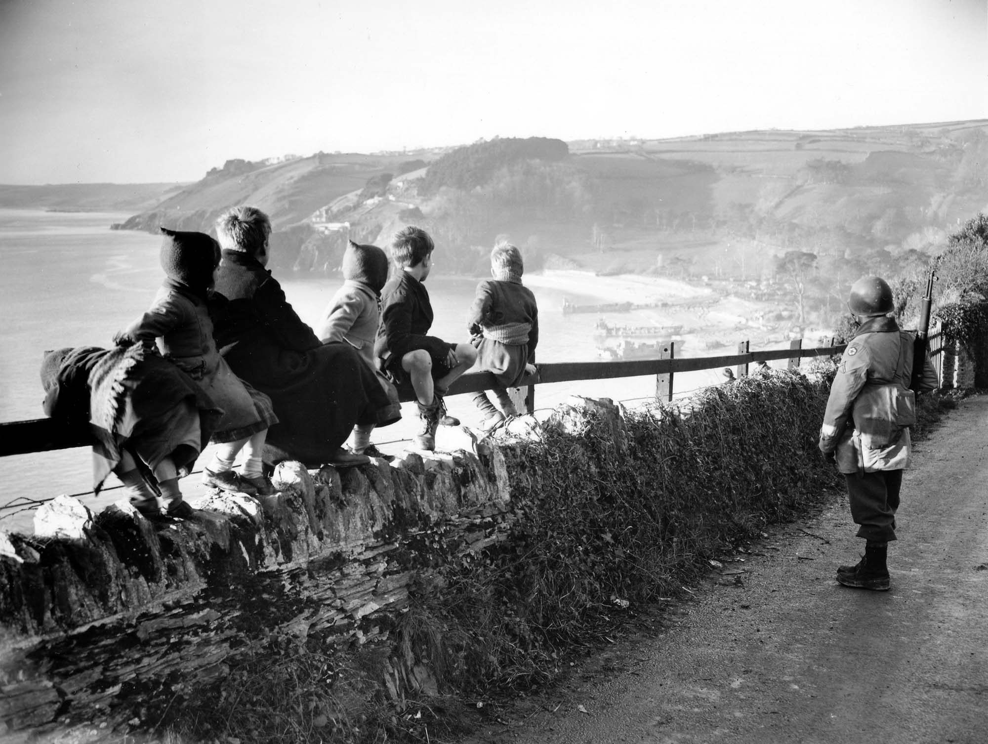 a black and white photo of children on a country lanne looking down onto a beach as a soldier stands nearby