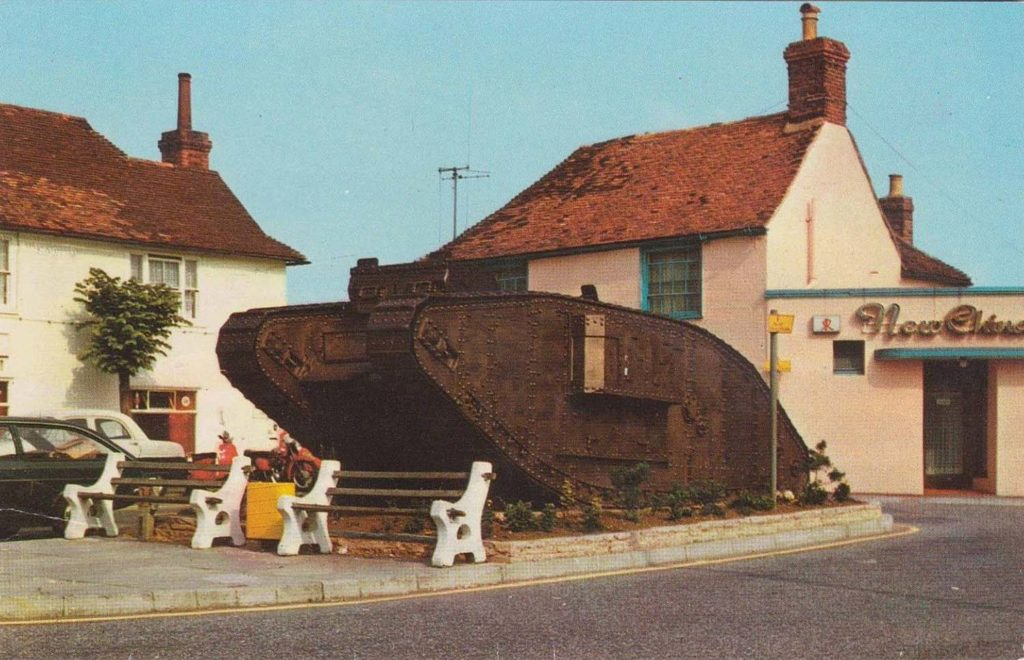 a colourise postcard showing a tank next to two old buildings