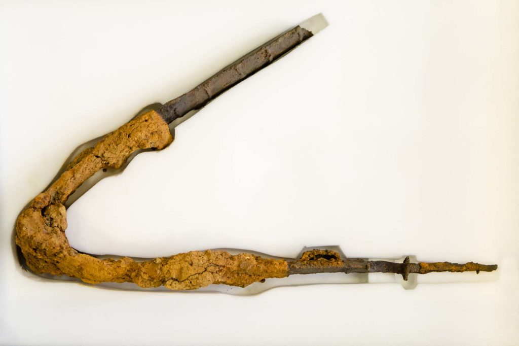a photo of a bent rusted spear.