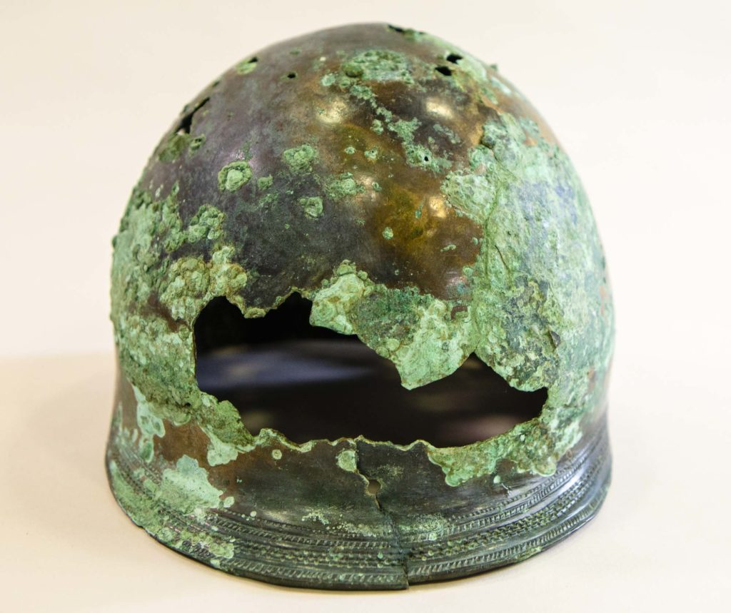 a photo of a helmet with a hole in its front and covered in verdigris