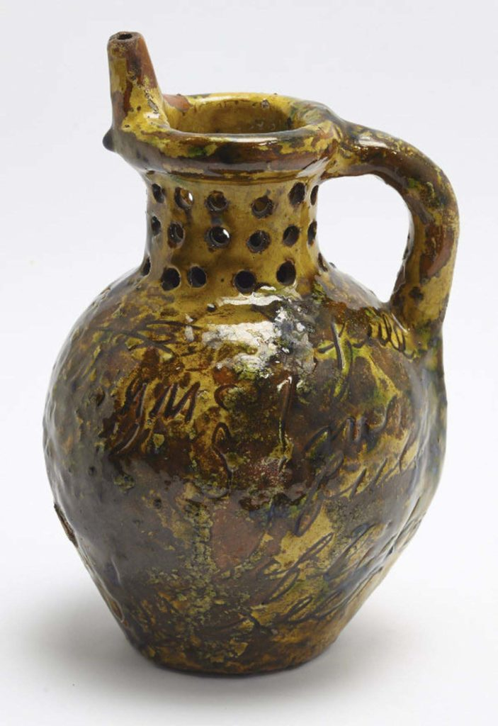 a photo of a handled ceramic jug with holes in its neck