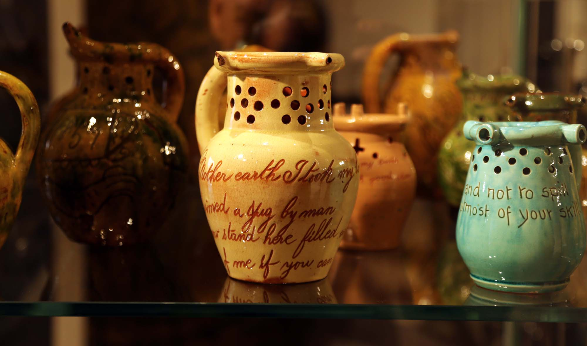 a photo of a collection of jugs with holes in their necks and mottos on their bodies