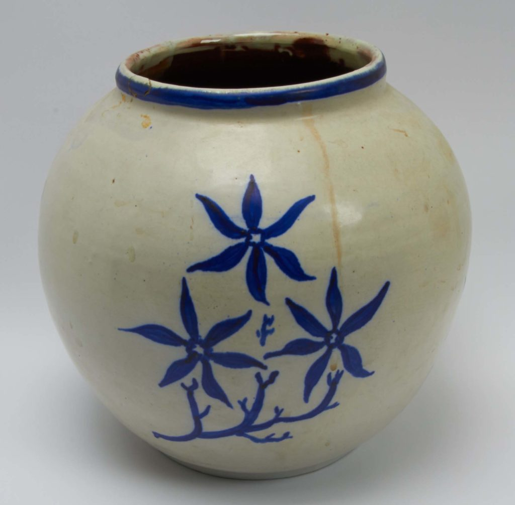 a photo of a simple ceramic pot with blue floral design