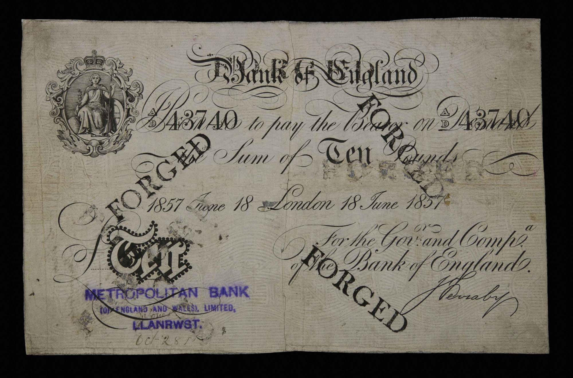 an old ten pound bank note with 'forged' stamped across it