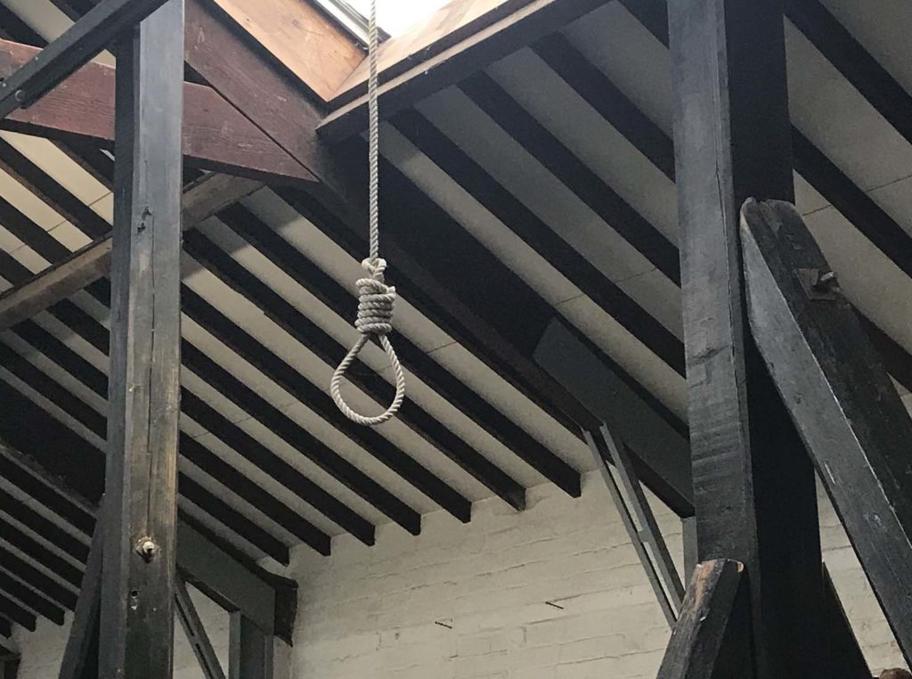 a photo of a rope noose hanging from a gallows cross beam