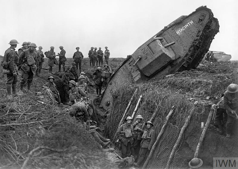 a photo of a tank resting with its front end iin a trnch filled with British soldiers