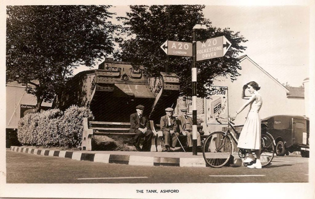 a black and white postcard photo of a tank with two old men sat on a bench in front of it while a girl in white dress with a bicycle stops in front of them