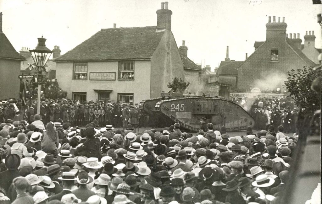 a black and white photo of a tank arriving in a town full of crowds