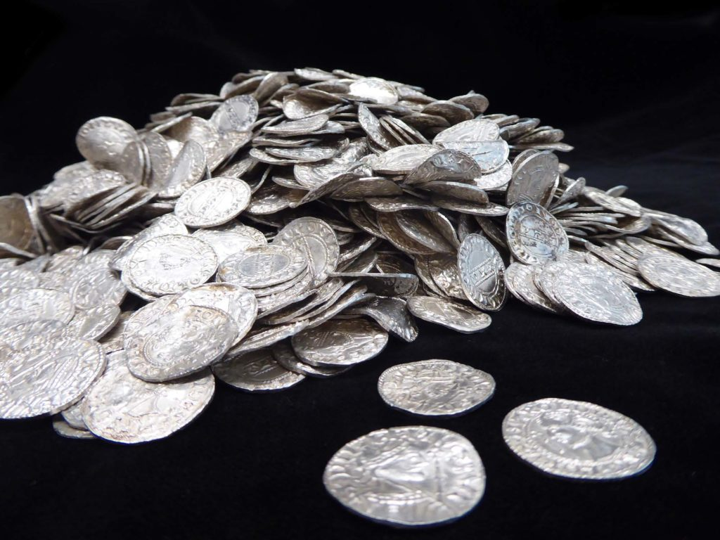 a photo of a silver coin hoard against a black background
