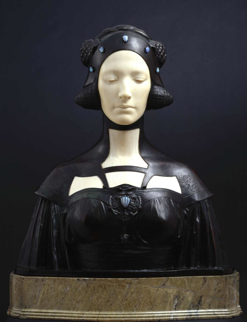 an art deco sculpture of a woman in alabaster with black headdress resembling a flight helmet which is connected to a dress