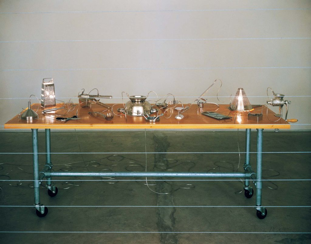 a photo of a spartan table laid with various kitchen implements and wires