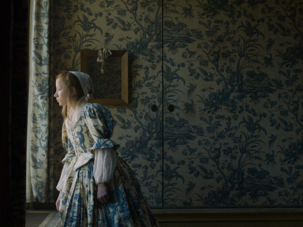 a photograph of a woman in period clothing peering out of a window from a wallpapered period room