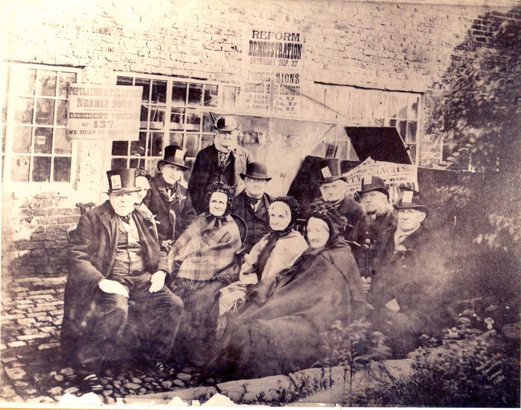 an old photograph sowing a group of elderly people in Victorian top hats and bonnets
