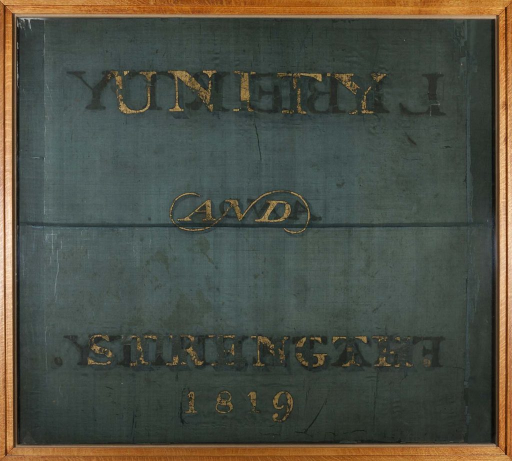 a photo of a banner with the words Unity and Strength in gold lettering