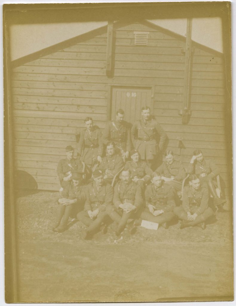 a sepia tinted photo of soldier officers outside a Nissan hut