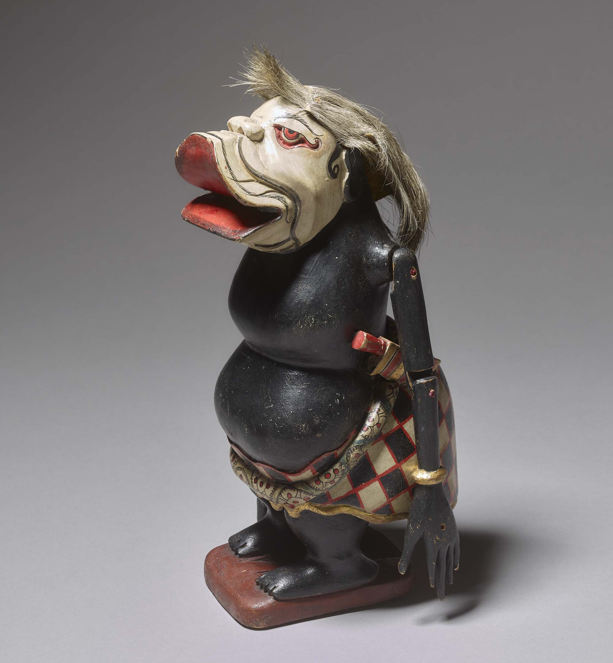 a puppet figure with a white pig like face, short black body and swollen stomach