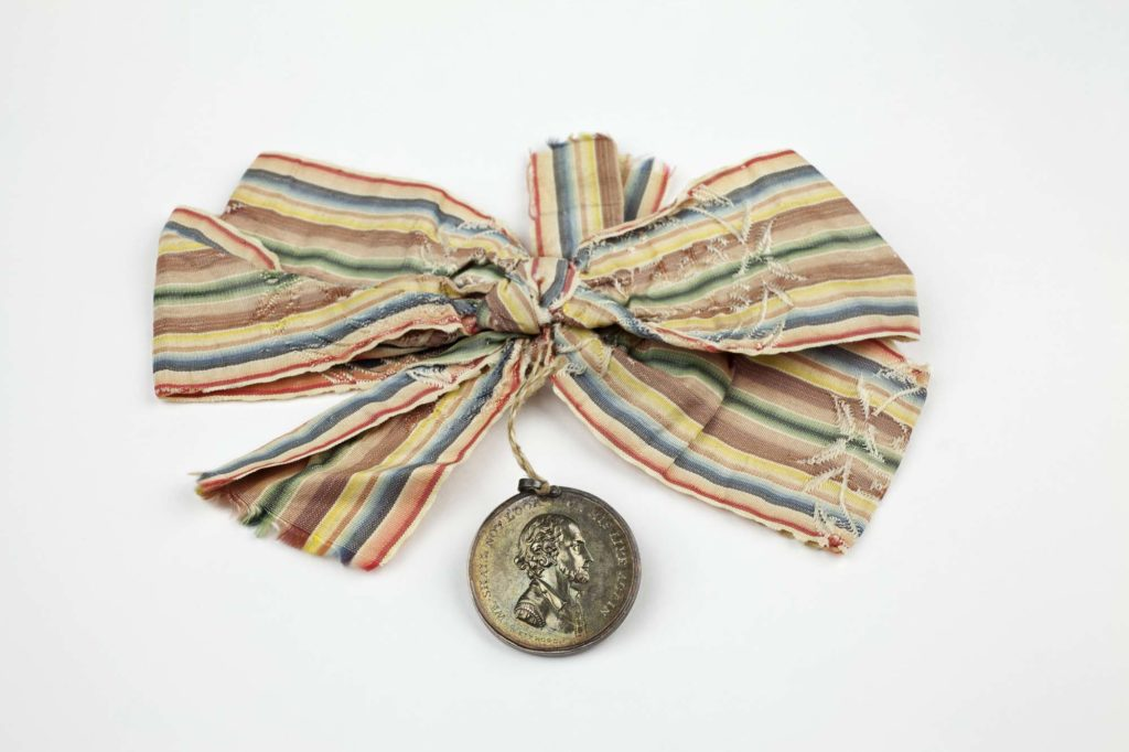 a photo of a medal on a long striped ribbon
