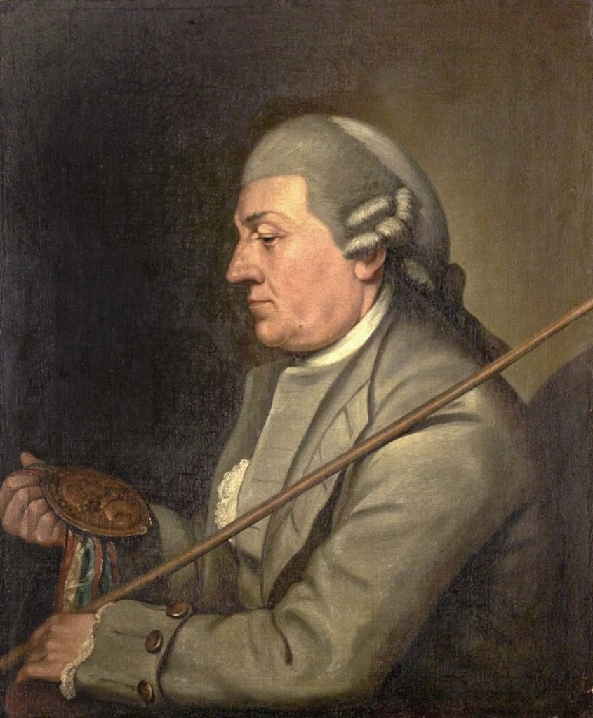 a photo of a man wearing a Georgian-style wig in side profile