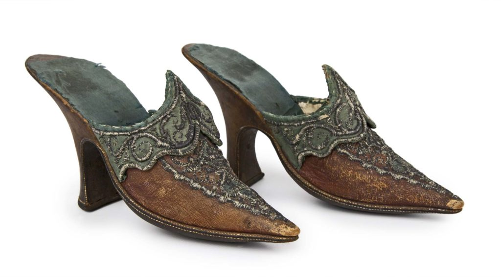 a pair of open backed, high heeled pointy shoes in tan leather and silver brocade
