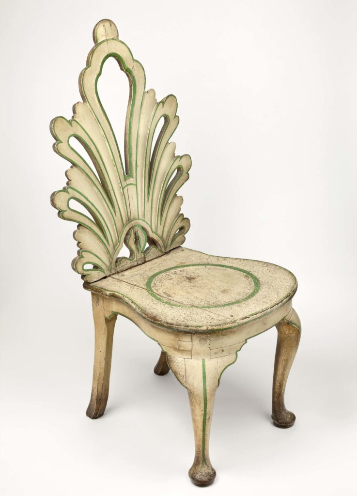 a pierced back chair of conventionalised acanthus form, above a saddle-shaped seat turned with a depressed ring; raised on a shaped frieze with pad-foot cabriole legs to the front. The rear feet are chamfered and swept and retain the original scheme of white paint, lined green.