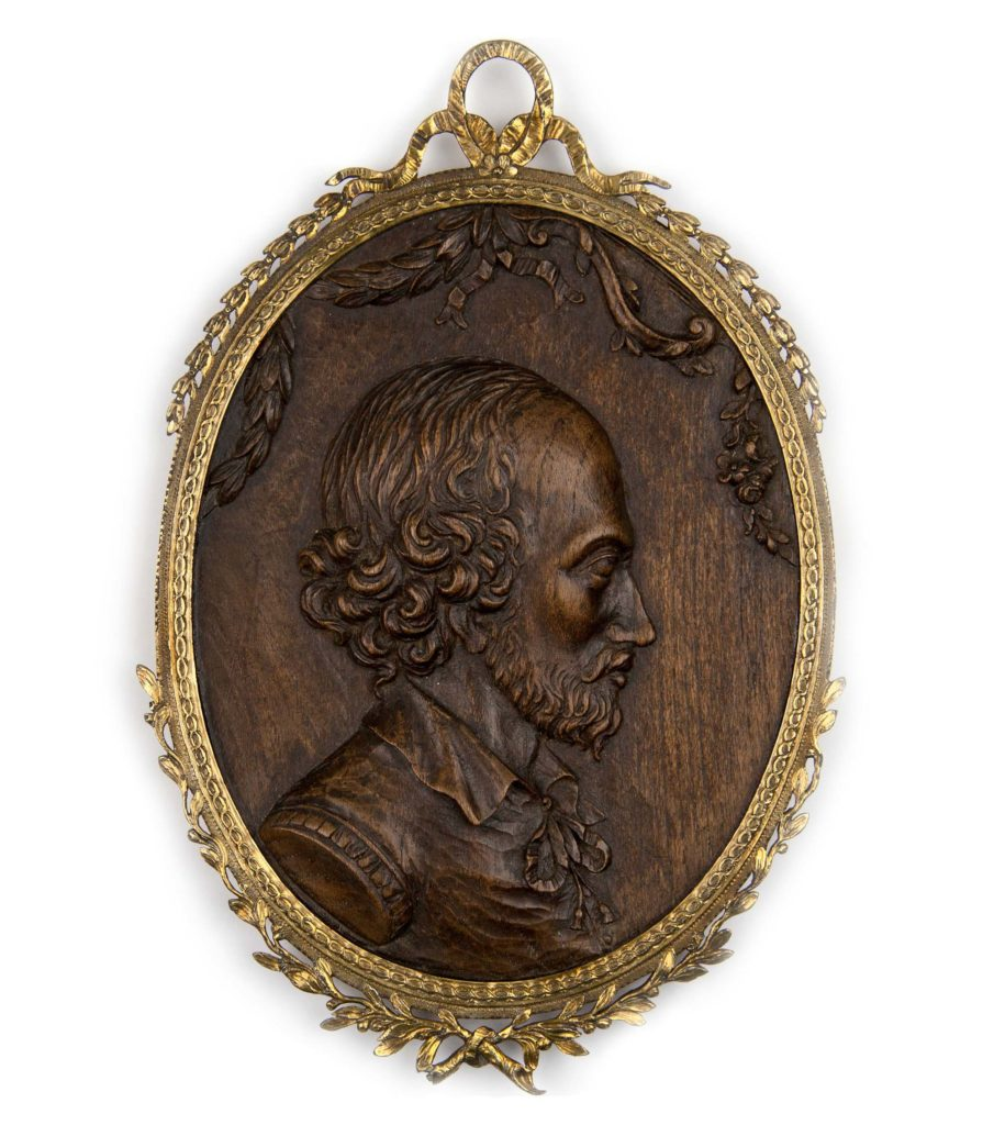a wooden carved medal with the image of shakespeare on its front