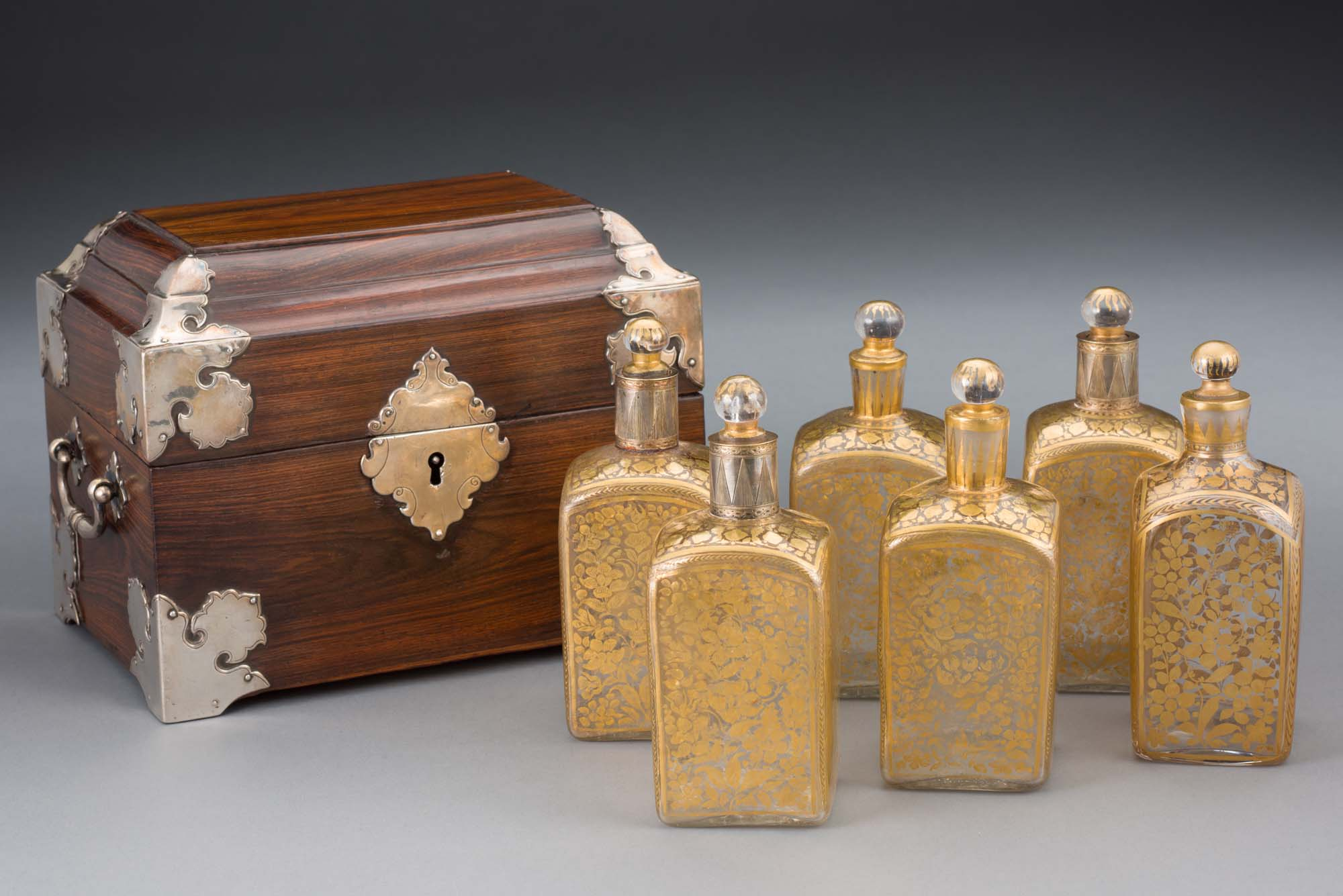 a small wooden case with six golden flasks lined up next to it