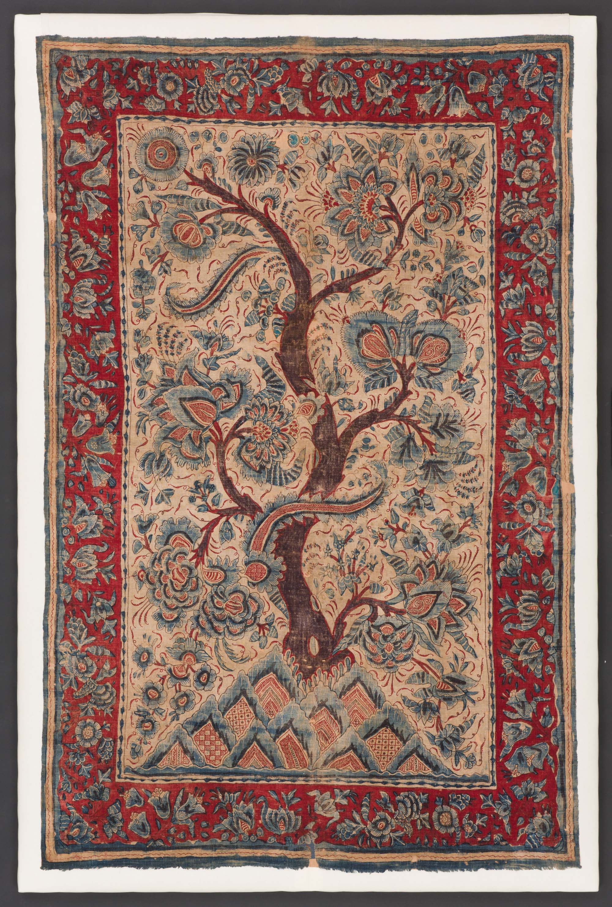 an embroidered wall hanging with central tree motif