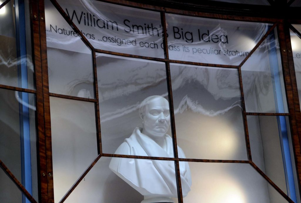 a photo of a bust of a man behind a glass case