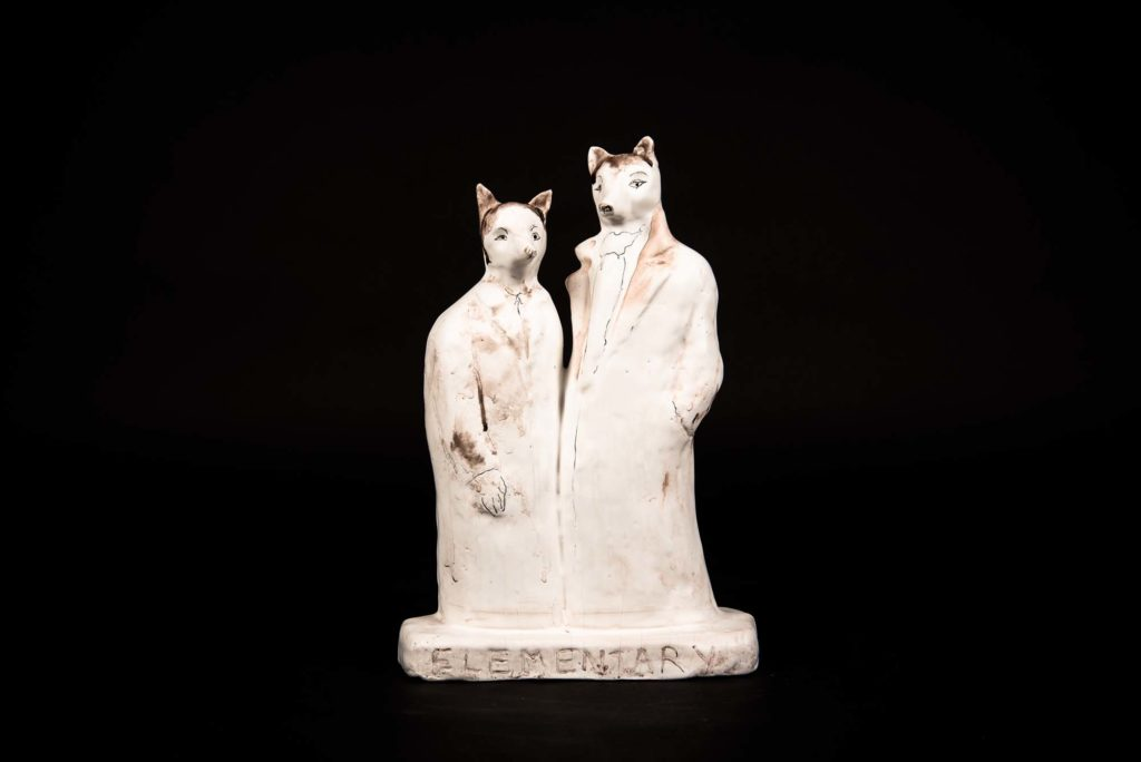 a photo of two porcelain foxes in the pose of two people