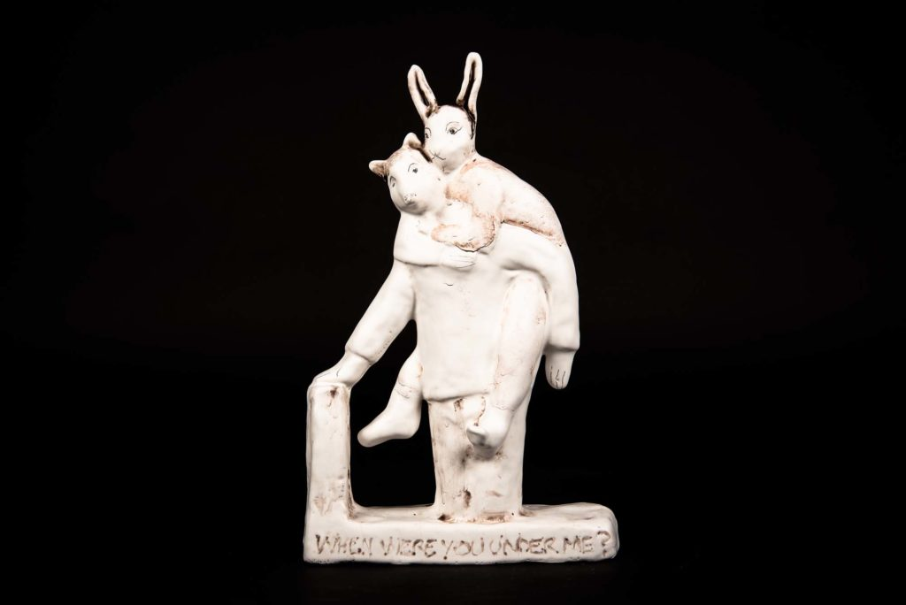 a porcelain figure of a hare climbing on a badger's back