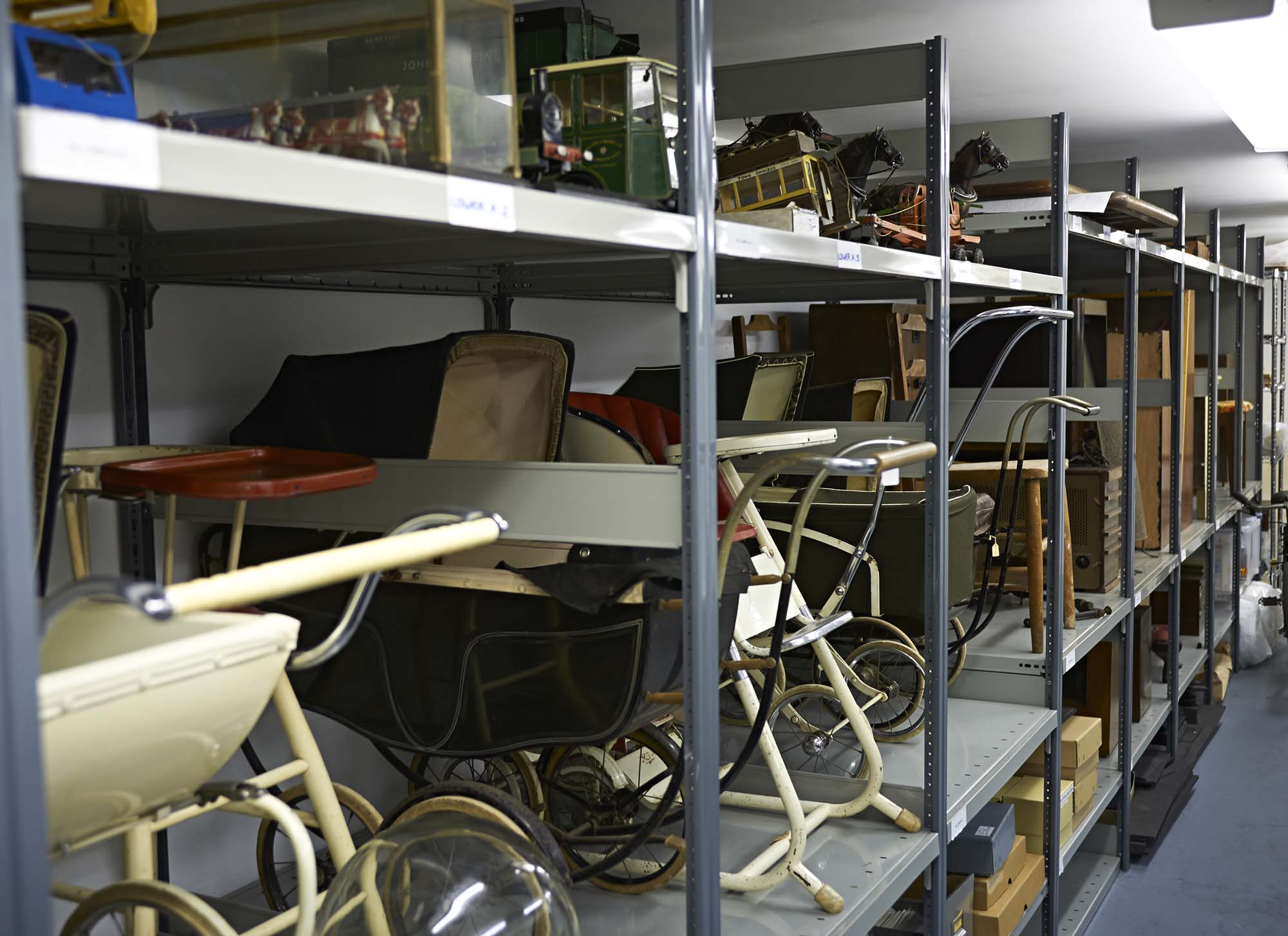 a photo of a store room with rack shelving holding a prams and other items of domestic furniture