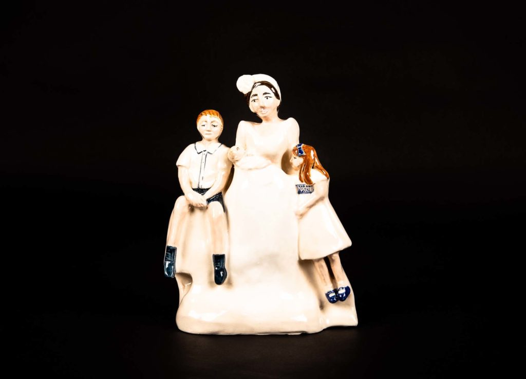 a staffordshire flatback style porcelain with three figures of a woman and two children