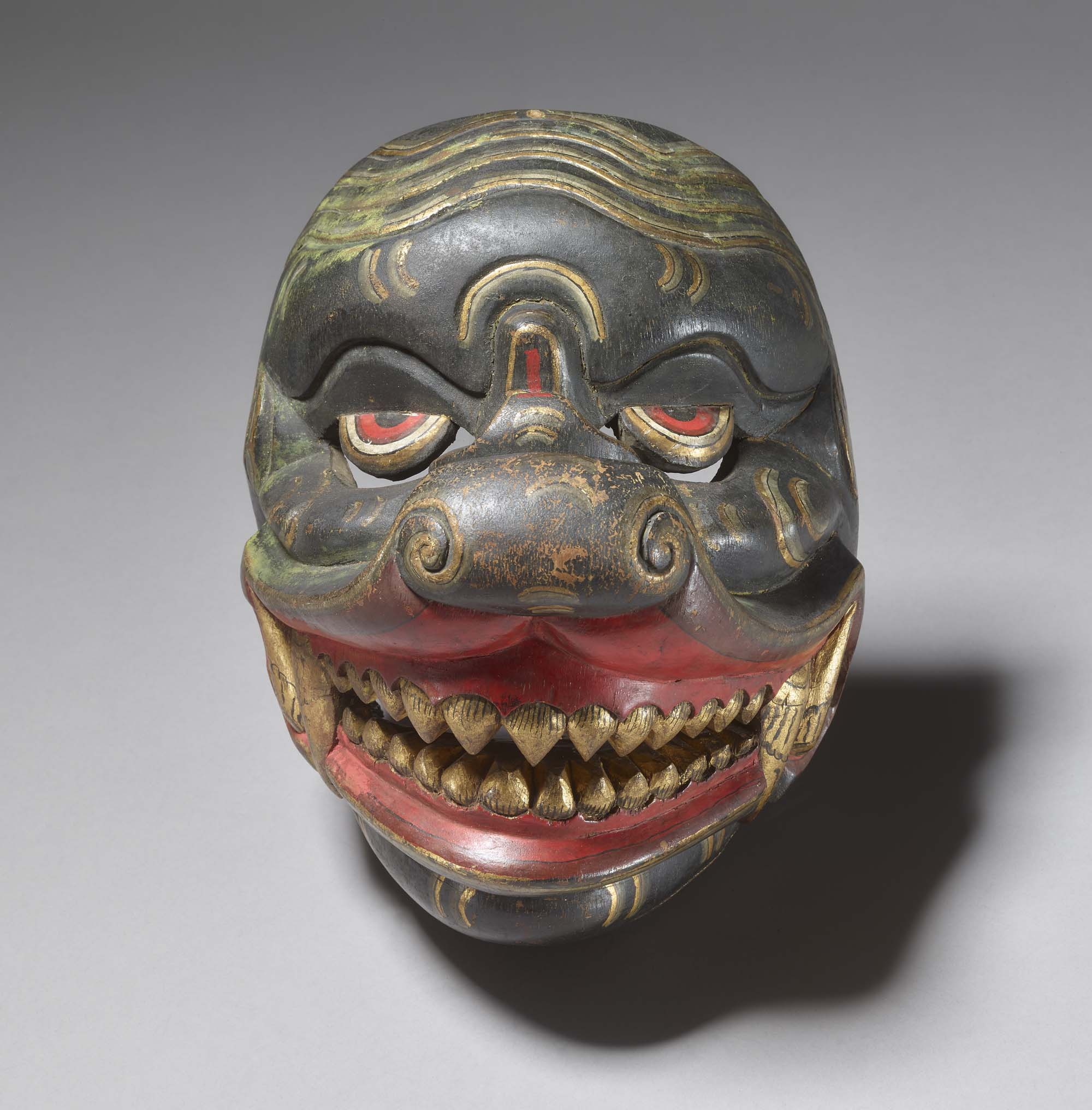 a decoarted mask with green skin and yellow teeth in red gums