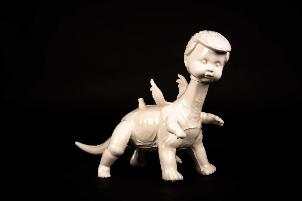 a photo of a ceramic figure dinosaur toy with a male doll's head on it