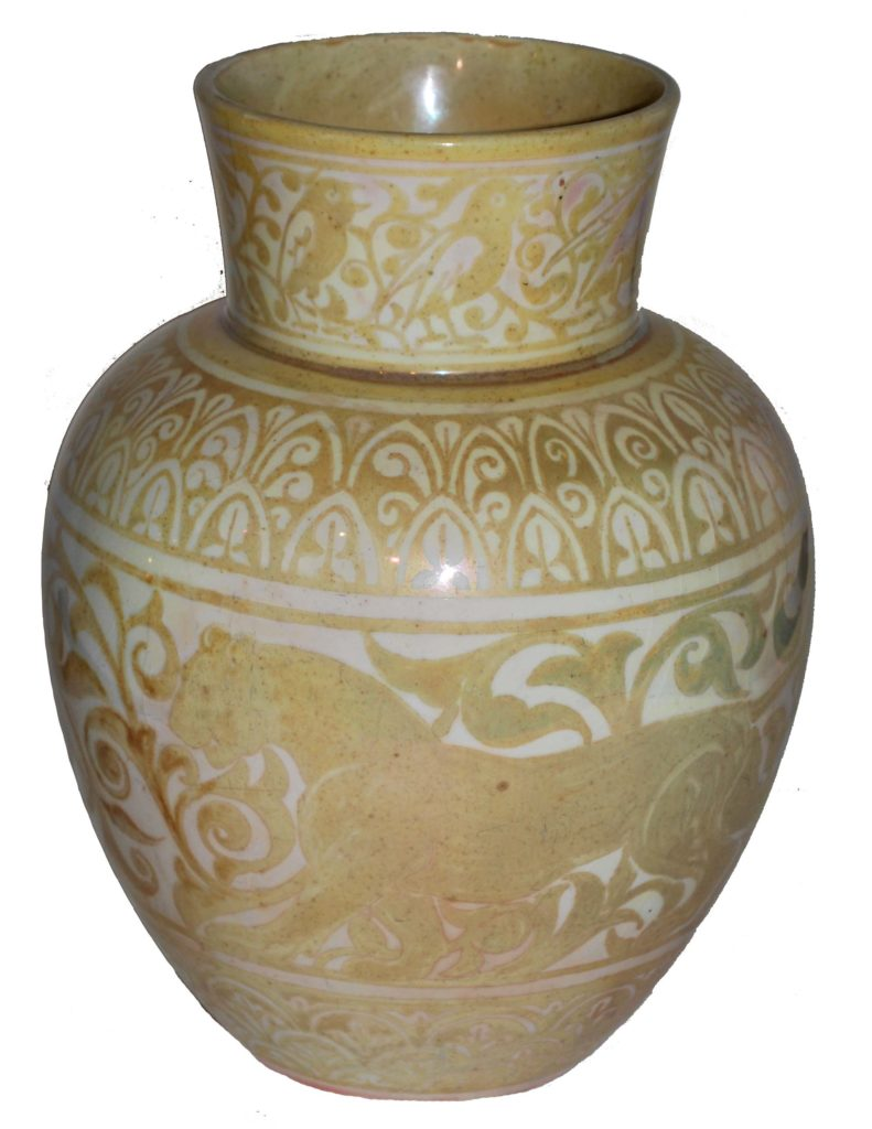 a ceramic jar with fluted neck and subtle lion pattern in a gold against a light brown