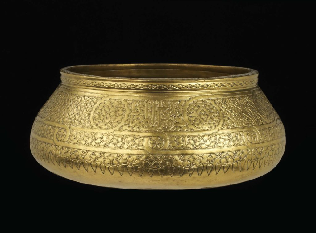 Bowl of engraved brass inlaid with silver; decorated with inscriptions of titles interspersed with roundels containing alternately birds and interlaced plants with central whirling rosettes