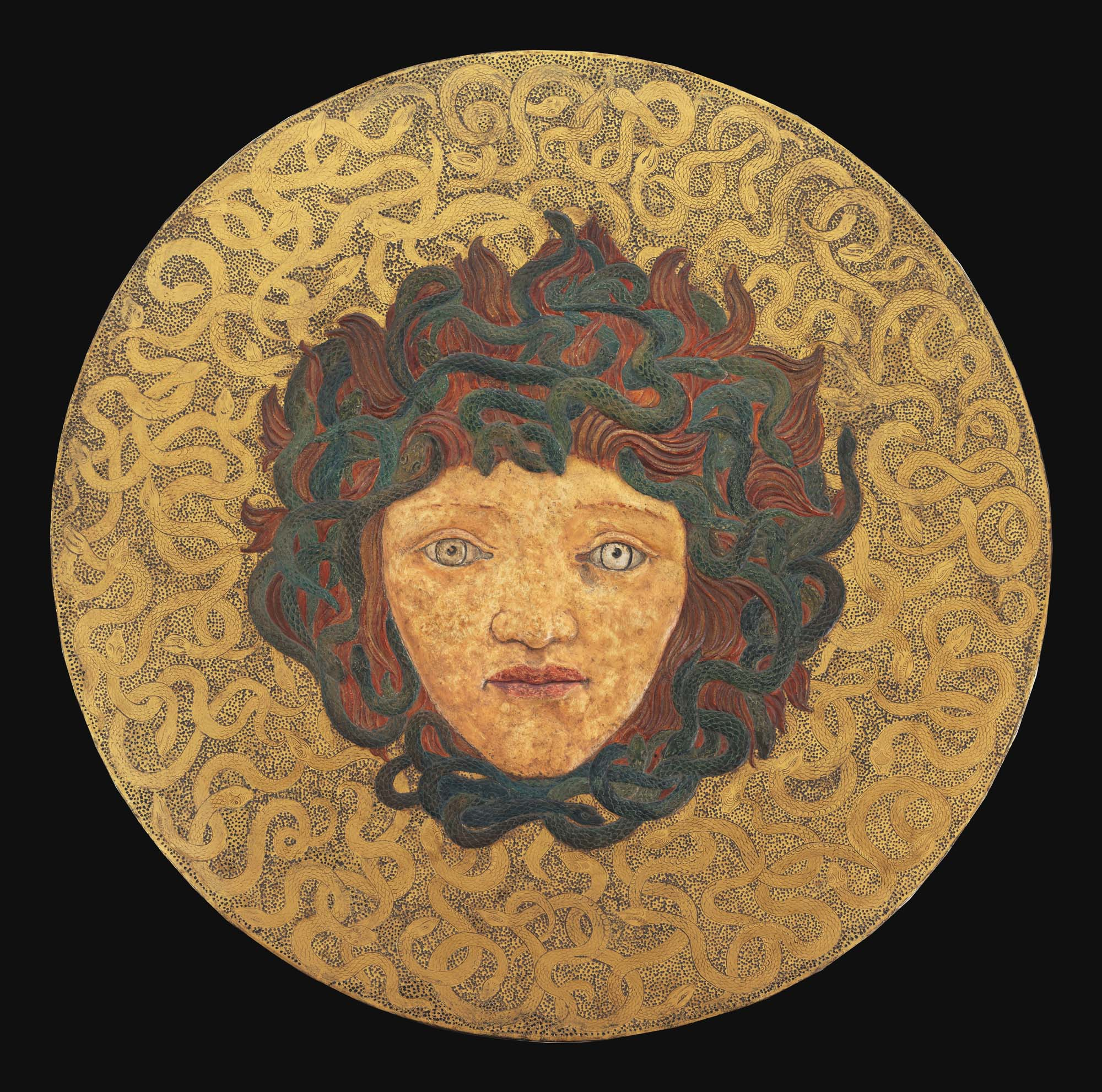 a decorative panel in gold with the head of the Medusa