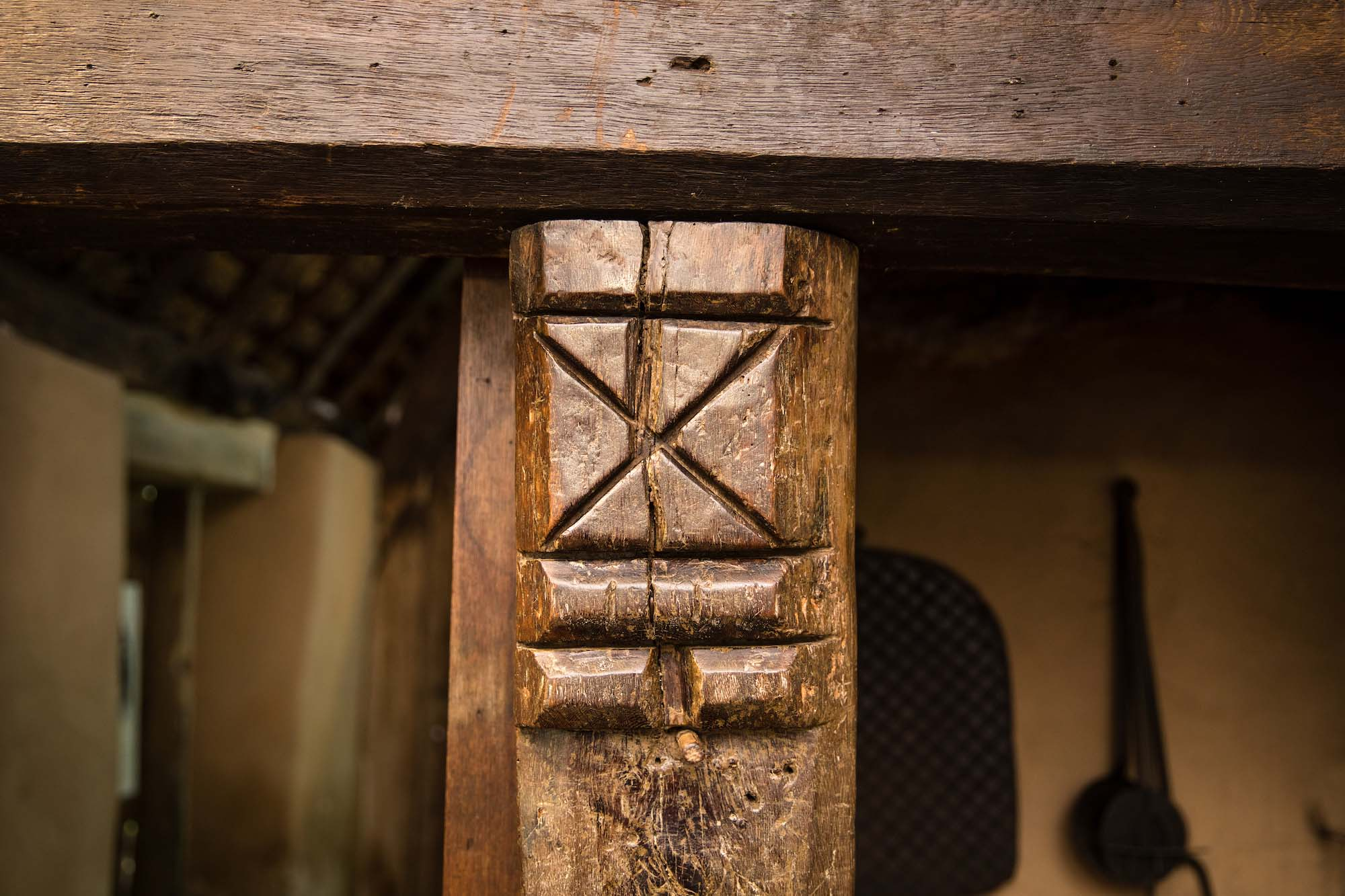 a photo of a carved wooden post holding up a beam