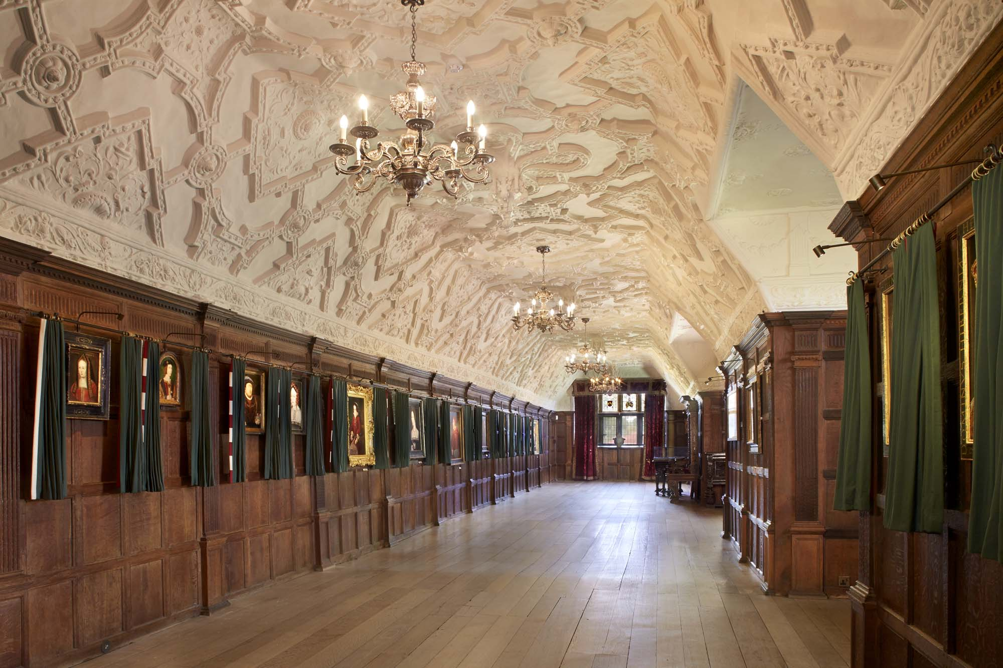 a photo of a long wood panelled room with stucco ceiling and portraits on the wall