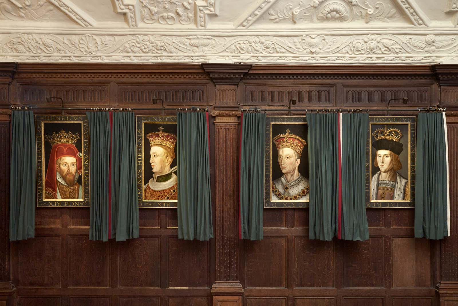 a photo of four king's portraits in curtained frames