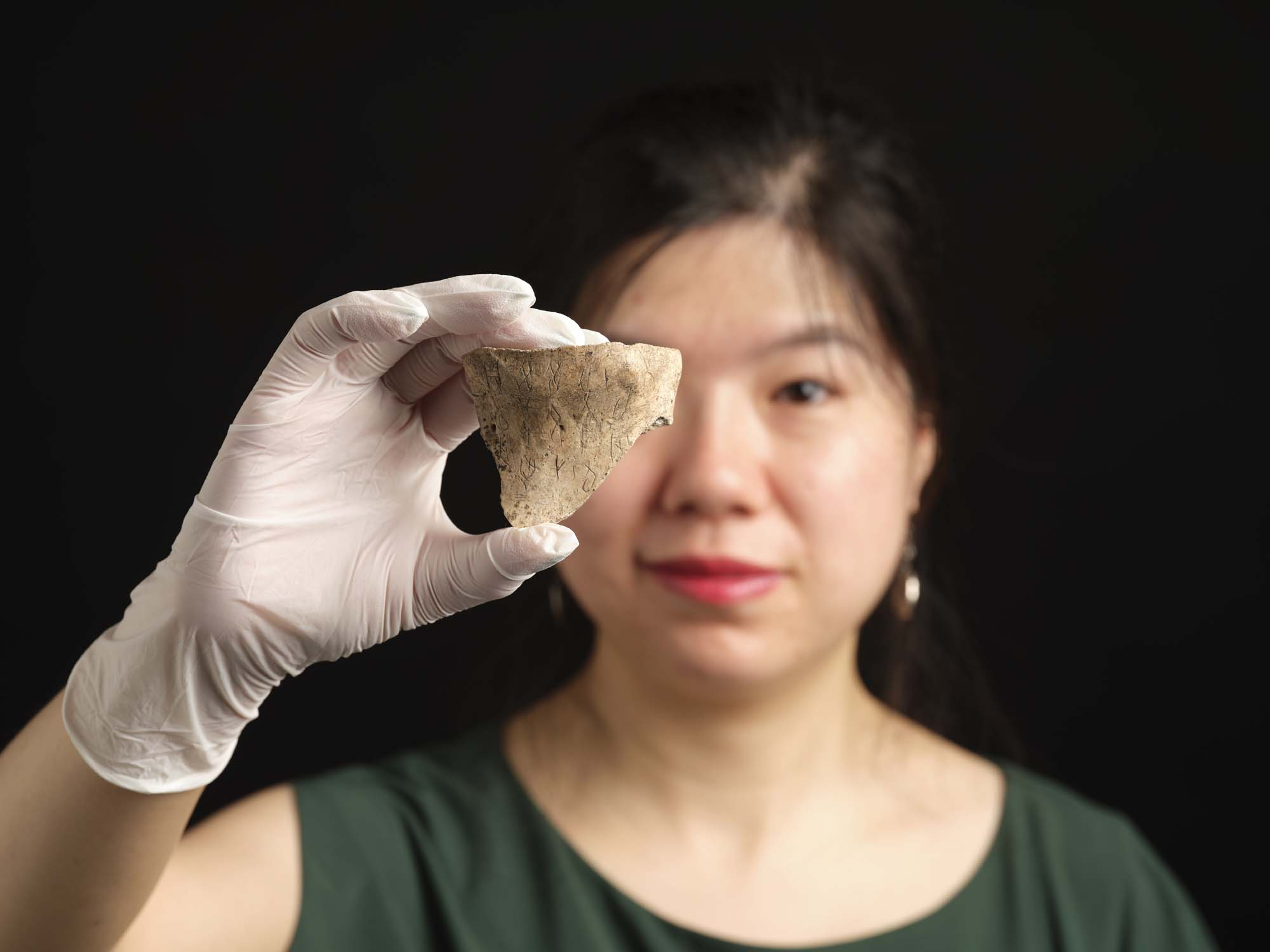 a photo of woman holding a scrap of bone in a gloved hand