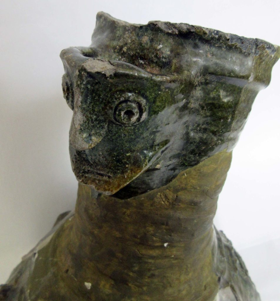 a photo of a pottery fragment with shape of a face in side profile