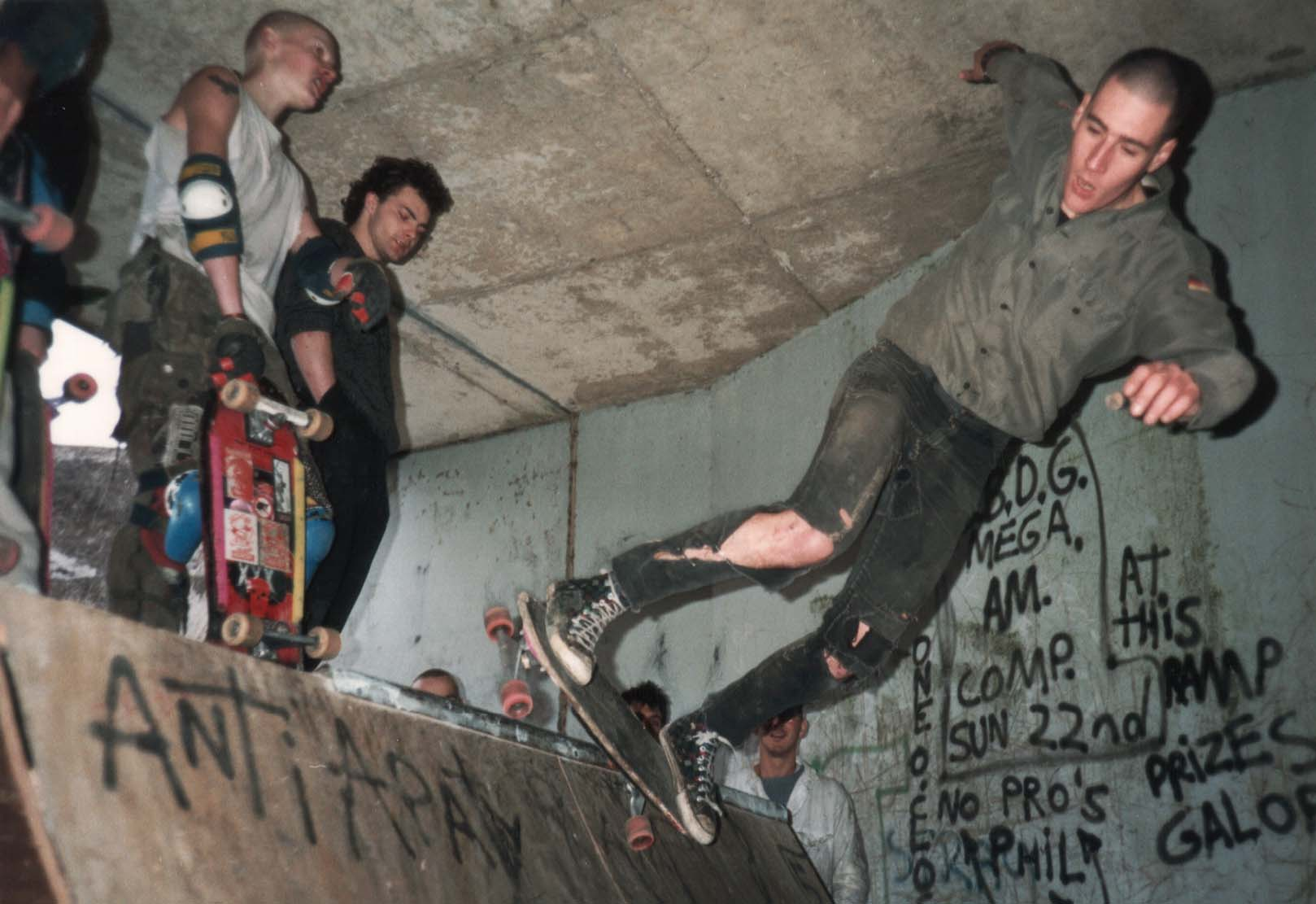 a colur photo of a young man in ripped jeans on a skateboard ramp