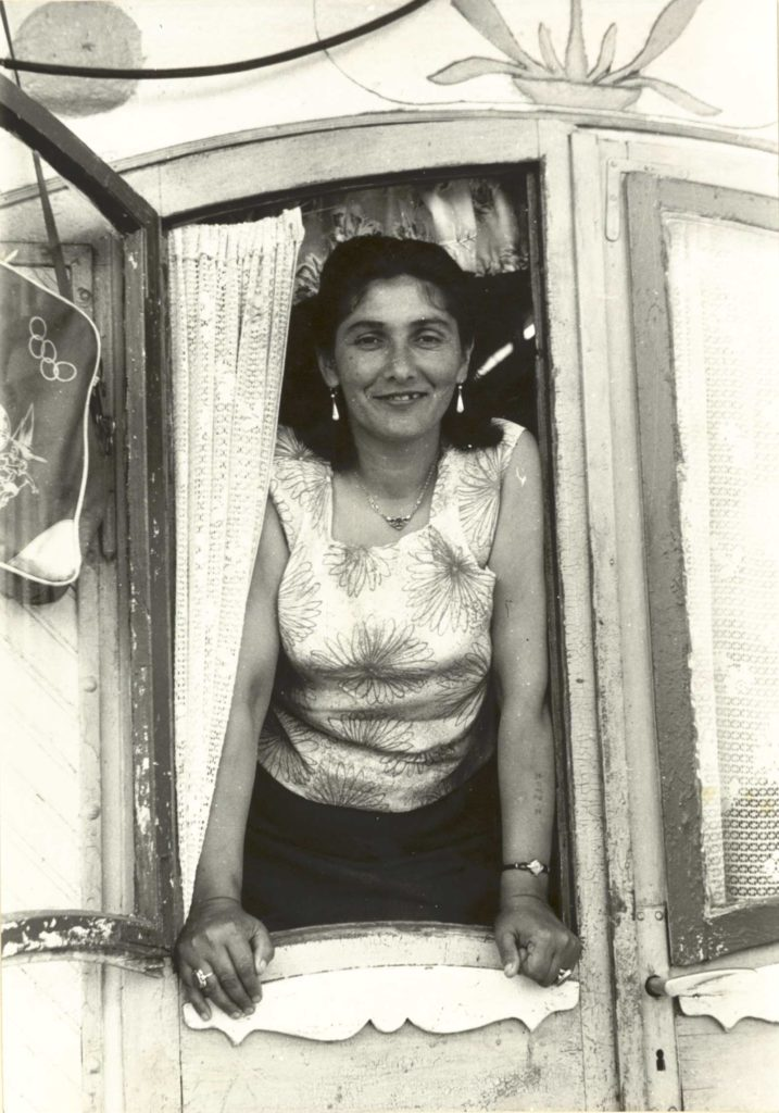 a photo of a womn smiling as she leans on the door of her wooden caravan