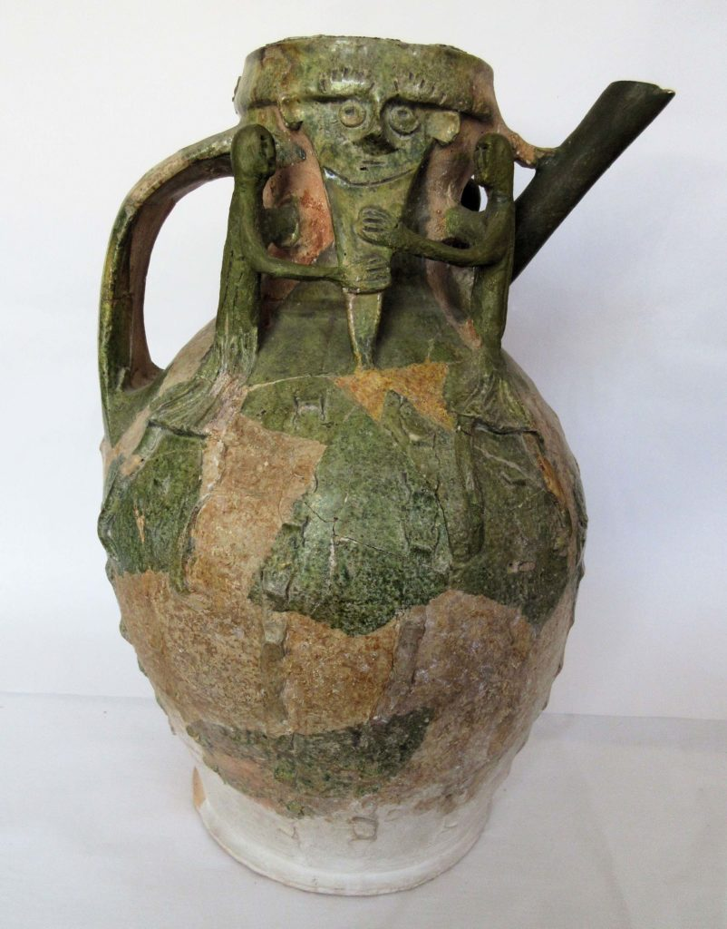a photo of an elaborate green vase with human faces on it